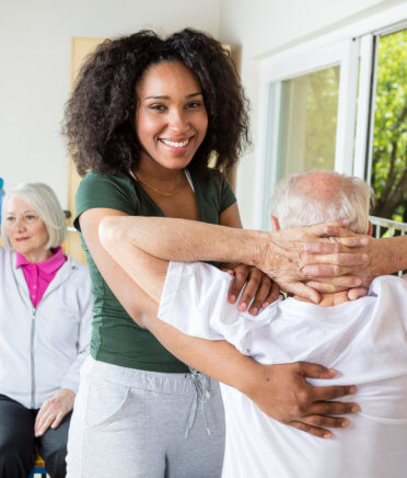 caregiver and elderly man doing physical therapy
